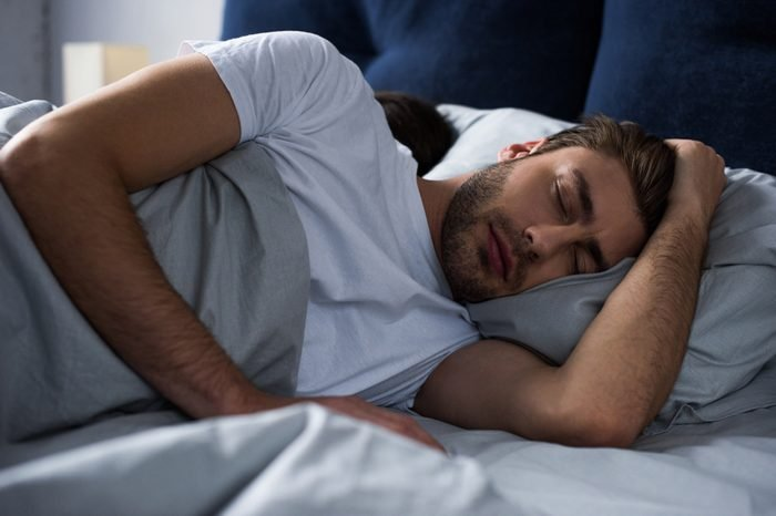 Young man sleeping by his wife in bed