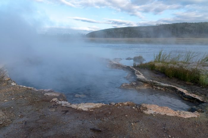 Steamy river water and muddy shoreline with green grass under blue sky with white fluffy clouds.