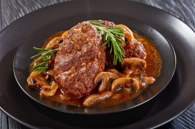 portion of delicious hot savory juicy salisbury beef steaks with mushroom onion gravy served on black plates on wooden table, view from above