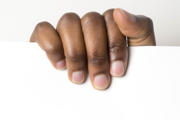 Close up of African American man dark brown skin woman hand and holding blank white advertising card