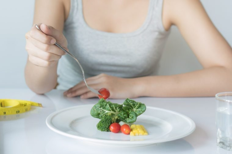 Eat less and eat healthy. person eating vegetable in dinner during control calories on dieting.