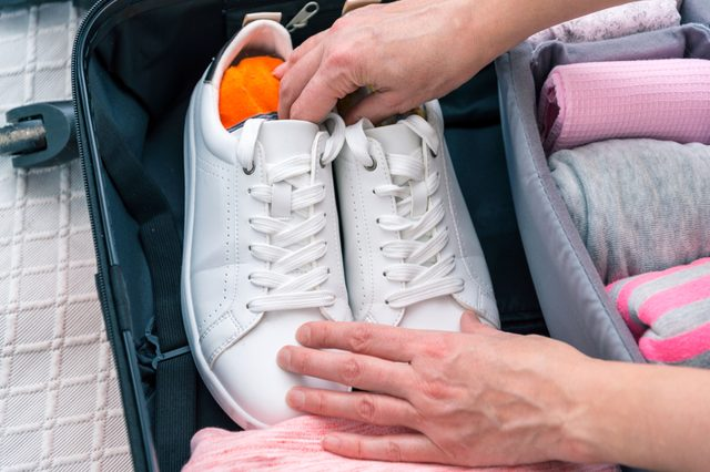 Woman hands puting shoes to suitcase, bag organizer