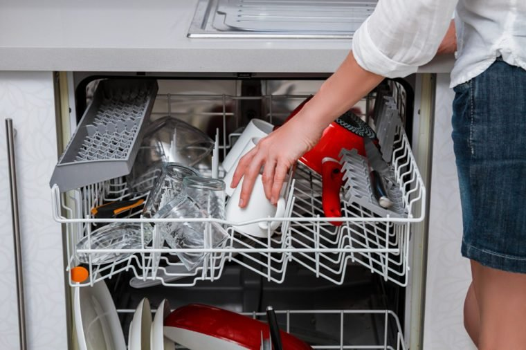 Elegant woman washing dishes in the dishwasher.