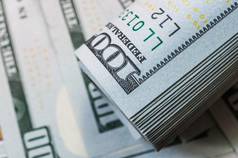 Roll of hundred dollar bill on dollar bills background.