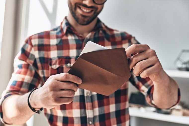 Receiving greeting card. Close up of young man opening envelope and smiling while standing indoors