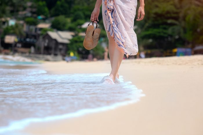 legs of woman with shawl wearing, holding in hand slippers, walking on the fine white sand of the sea beach, feeling comportable and relax in long weekend and holidays