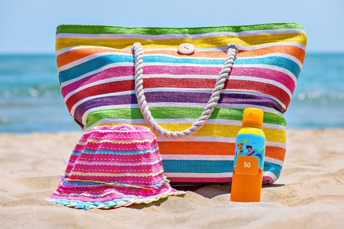 Bottle of sunscreen lotion on the sandy beach.