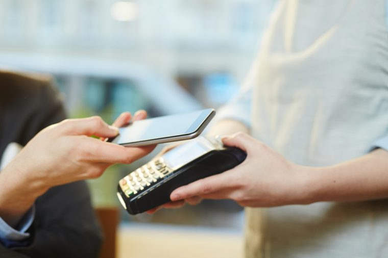 Close-up view of unrecognizable waitress holding terminal and male guest paying for meal with modern smartphone