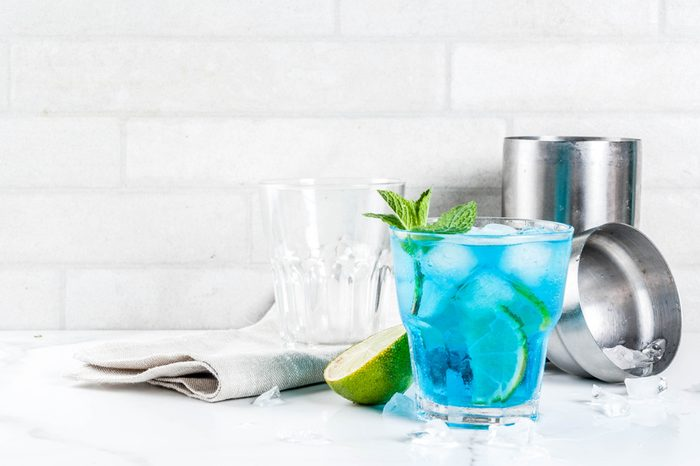 Colorful summer beverage, iced blue lagoon alcohol cocktail drink with lime and mint, white marble background copy space
