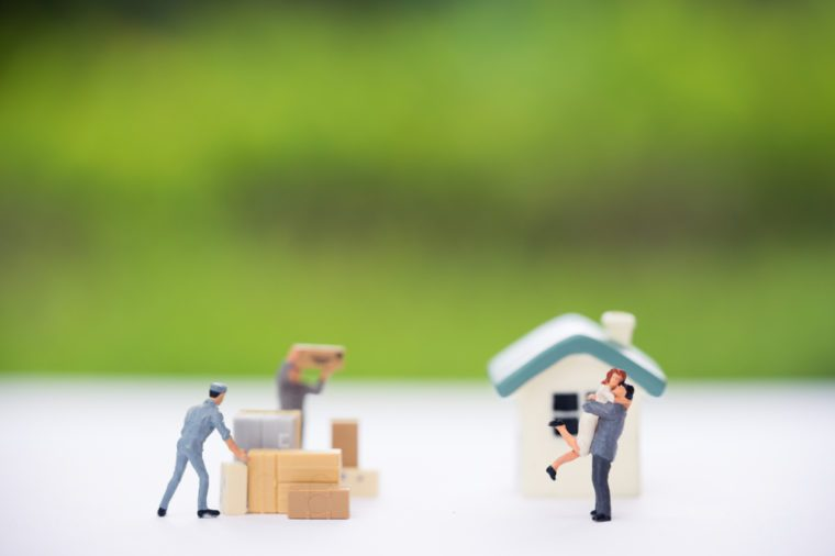 Miniature people, couple in front of new house and workers moving stuffs. Concept of moving house, relocation.