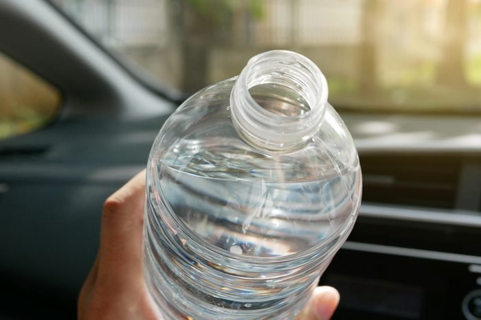 Selective focus of pure drinking water in a bottle about to be drunk in a car in the afternoon of a sunny day