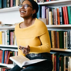 Positive african american young woman in stylish eyeglasses for vision correction laughing while received funny notification on modern smartphone device sitting with literature book in modern library