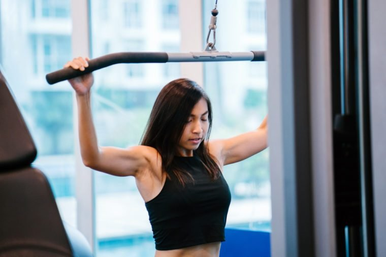 Portrait of a young Chinese Asian woman doing strength training at the gym. She is tanned, toned, muscular and fit and is focused on lifting the weights.