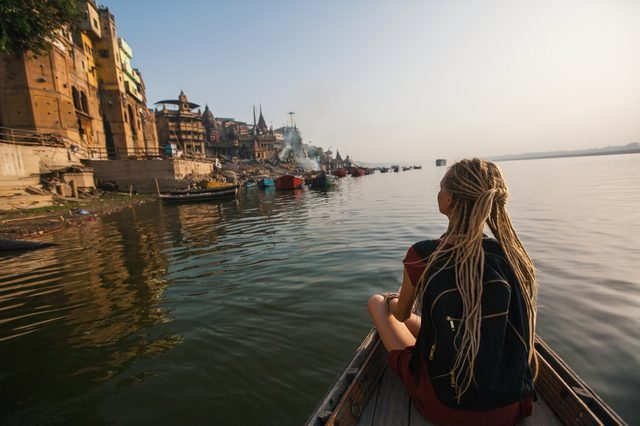 Woman traveler on a boat glides through the water on the Ganges river of Varanasi, India.