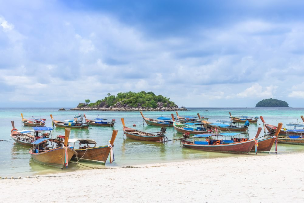 Group of Thai traditional longtail boats on white sand beach at Sunrise beach, Lipe Island, Thailand.