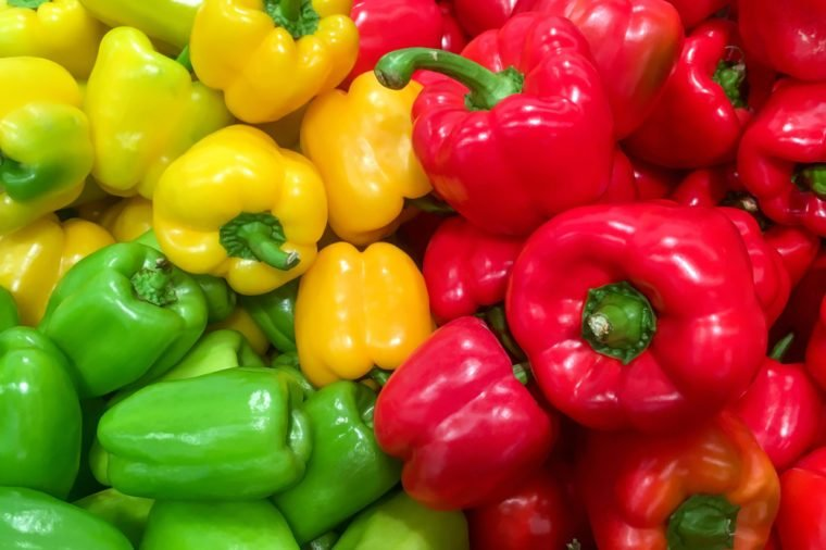 Food background - Pile of ripe red and green bell pepper close-up