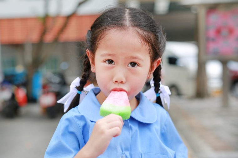 Adorable little Asian child girl in school uniform sucking or eating ice-cream in the park