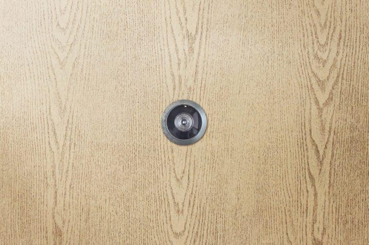 door lens peephole on light wooden texture