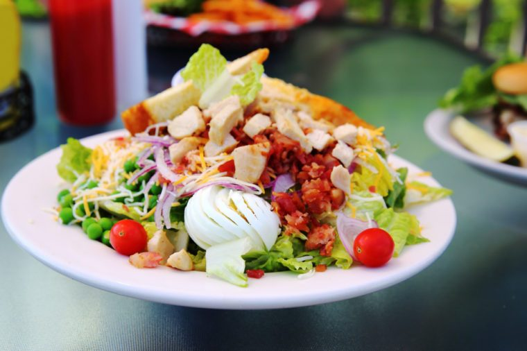 Crisp fresh lettuce with cherry tomatoes, bacon, and hardboiled egg adorn a chicken Cobb Salad
