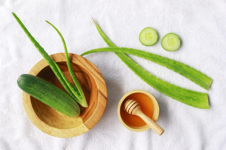 Aloe vera and cucumber with honey on white fabric background , herbal skin care concept.