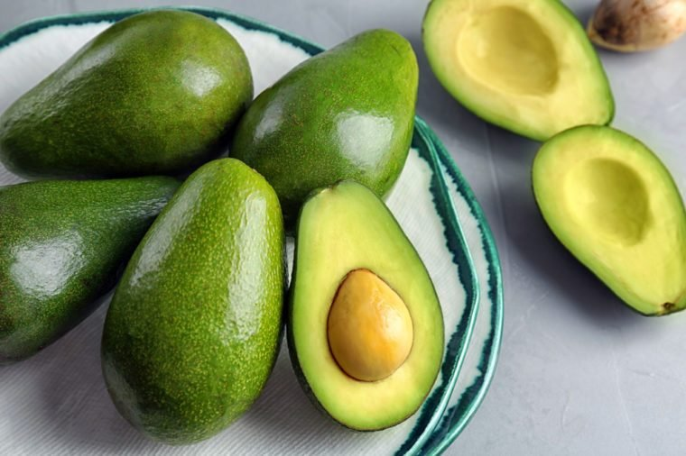 Plate with ripe avocados on grey table
