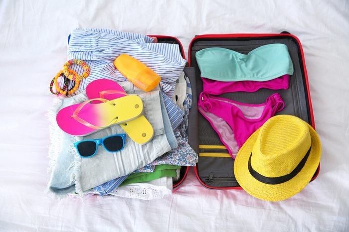 Open suitcase with different clothes and accessories for summer journey on bed