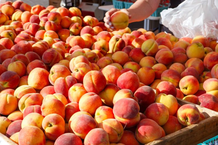 Customer picking up fresh peaches at an outdoor farmer's market