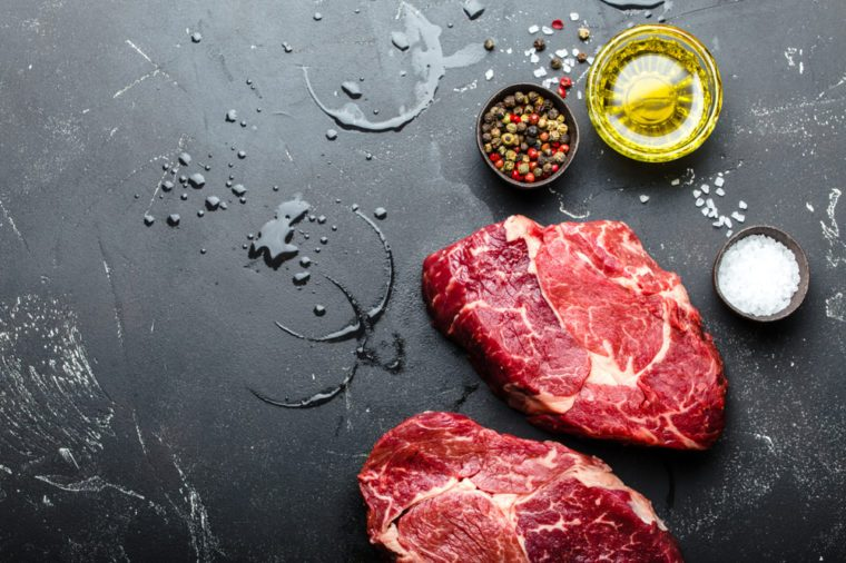 Close-up of raw marbled meat steak Ribeye on black rustic stone background with seasonings, olive oil for cooking, roasting, grill or BBQ party with space for text, top view. Meat restaurant concept