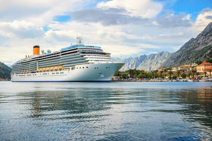 Big cruise ship in the port at the ancient city Kotor surrounded by mountains, Adriatic sea, Montenegro, Mediterranean summer landscape.