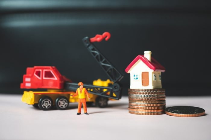Miniature people, engineer standing with construction vehicle, stack coins and mini house using as business, industrial and logistics concept