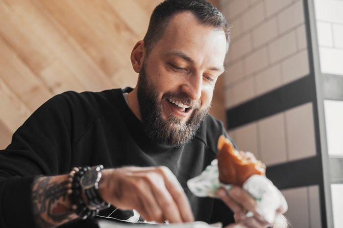 Young bearded man eating burger and smiling close up.