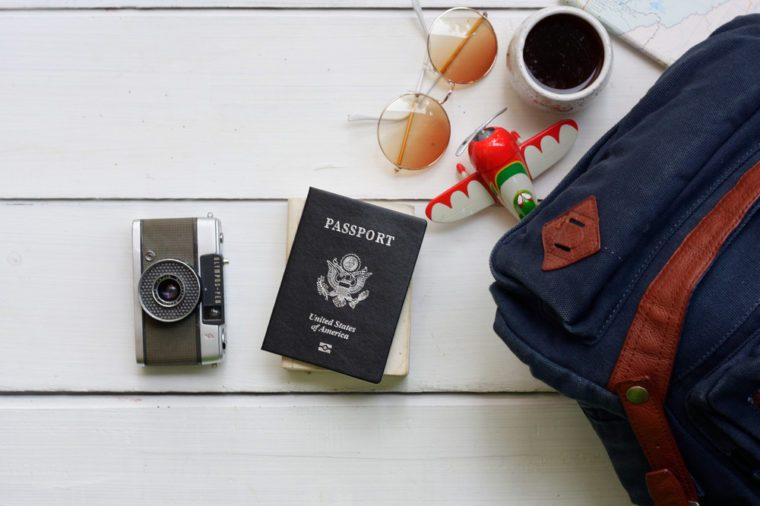 Passport of the United States of America with the concept of travel and equipment On the wood table Top view and copy space -Stock image Camera, Vintage, Glasses, Backpack, Coffee Mug, Drinks- Coffee