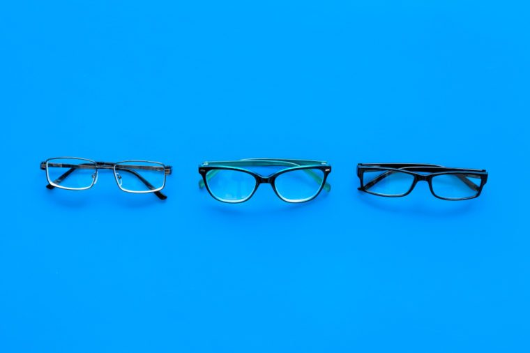 Glasses concept. Set of glasses with different eyeglass frame and transparent lenses on blue background top view copy space pattern