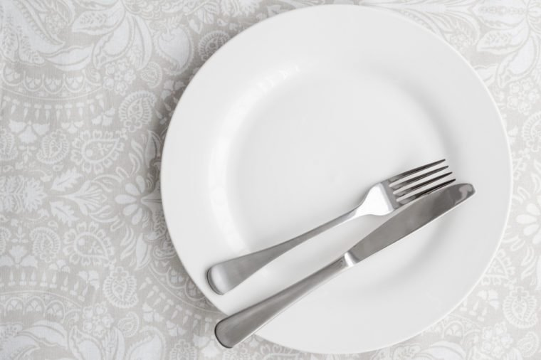 Knife and fork on white plate - top view photo