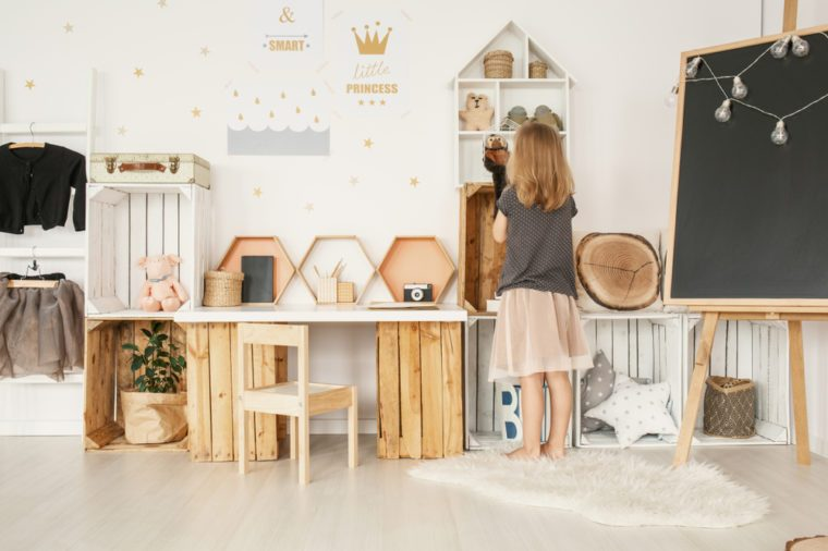 Little girl organizing her toys in white Nordic style bedroom interior with posters, wooden furniture, fluffy rug and blackboard with lights