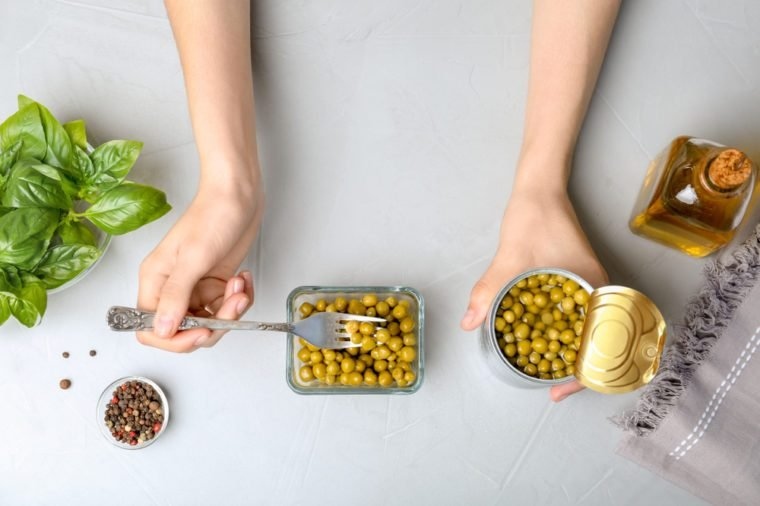 Woman with canned green peas at table, top view