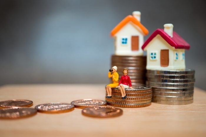 Miniature people, couple woman sitting on stack coins and mini house using as business and property concept