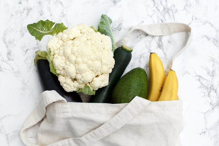 Set of products in a cotton eco bag on a marble table, bananas, avocado, eggplant, zucchini, cauliflower. The concept of zero waste.