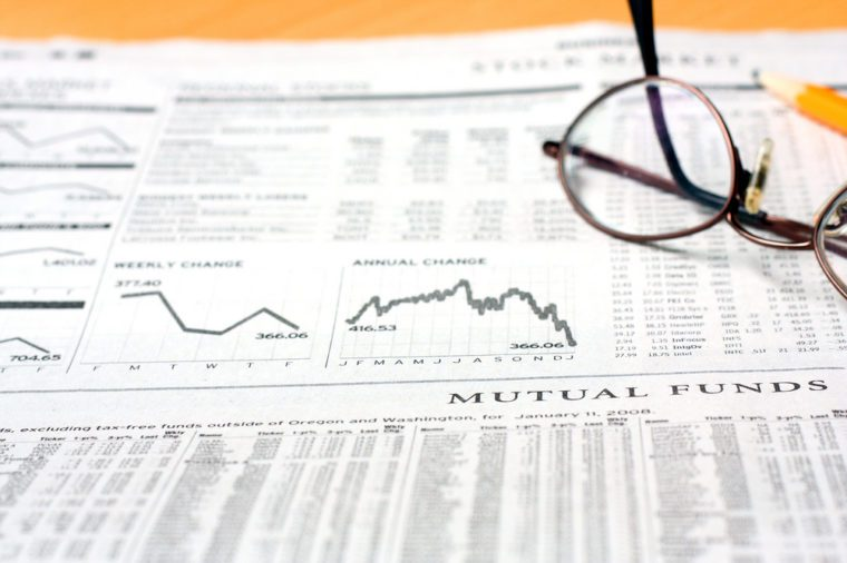 Newspaper with stock information with glasses and pencil, shallow depth of field