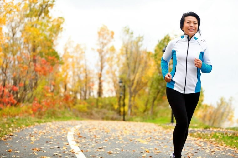 Mature Asian woman running active in her 50s. Middle aged female jogging outdoor living healthy lifestyle in beautiful autumn city park in colorful fall foliage. Asian Chinese adult in her fifties.