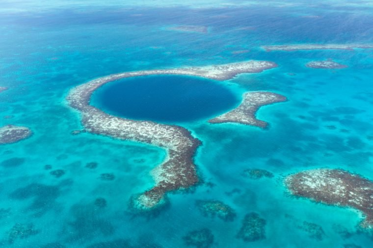An aerial view of the coral reef and deep cave that make up the famous diving spot of the Blue Hole in the Caribbean Ocean off the coast of Belize.
