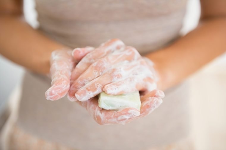 Closeup on young woman hands with soap bar