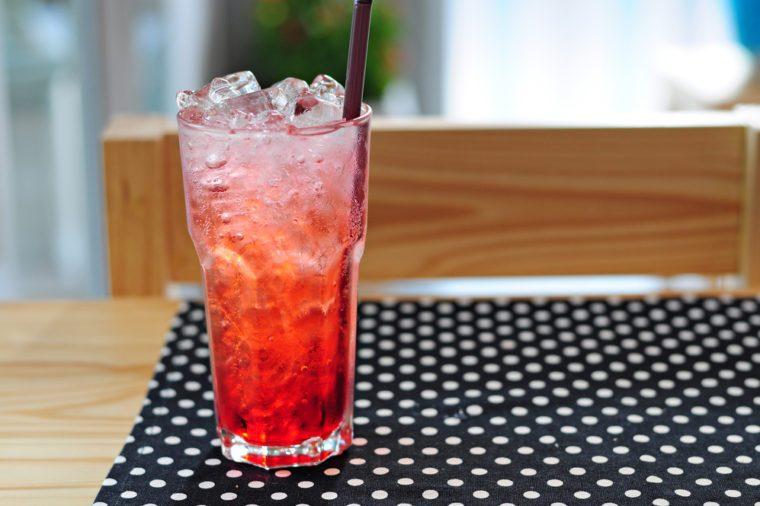 Strawberry italian soda on wood table with black polka dot tablecloth.
