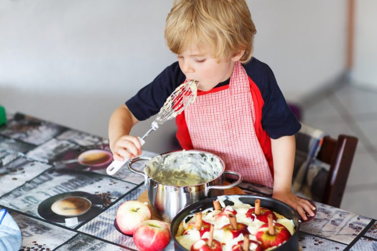 Happy little kid boy helping and baking apple pie in home''s kitchen, indoor. Tasting vanilla dough.