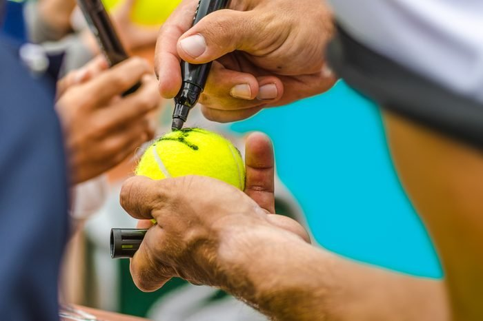 Tennis player signs autograph on a tennis ball after win, closeup photo showing tennis ball and hands of a man making signature, Australian open, US open.