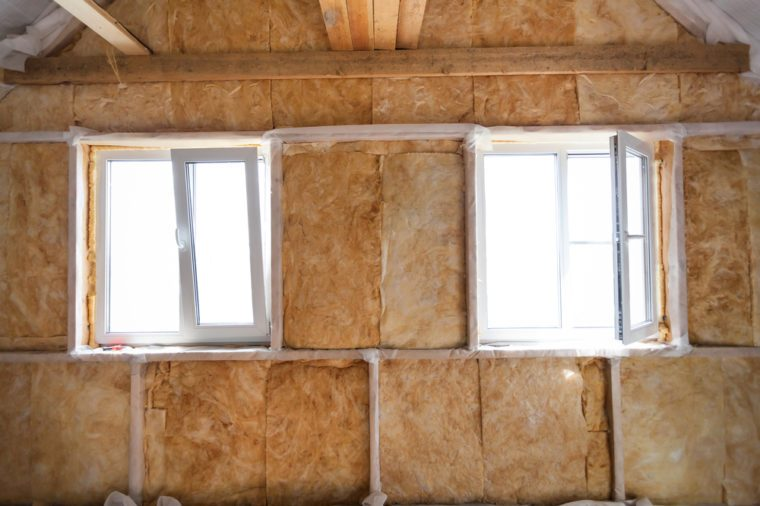 Inside wall heat isolation with mineral wool in wooden house, building under construction