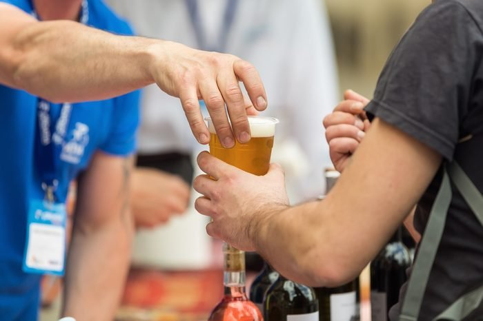 Bartender on the street bar handing a plastic glass of beer to a customer, holding the cup on top; during a street sporting event