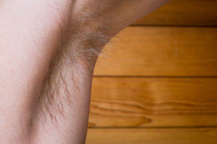 Young Guy's Hairy Underarm on Wooden Background