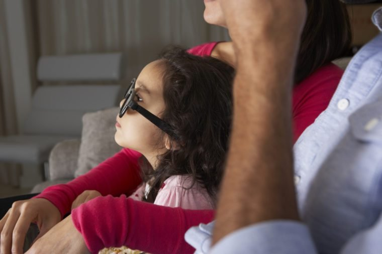 Family Watching TV Wearing 3D Glasses And Eating Popcorn