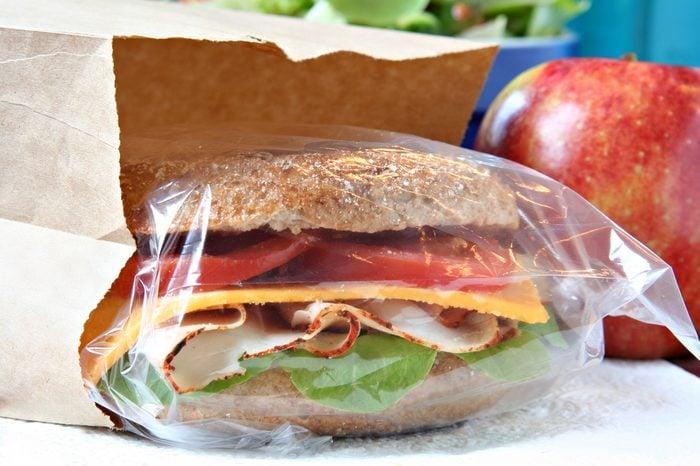 Whole grain sandwich in a brown paper lunch bag.